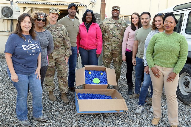 Tracey McGraw Howard, a contract specialist with the Regional Contracting Center-Afghanistan, Bagram Airfield, stands by her boss, Lt. Col. James Burkes, battalion commander of RCC-A, with other office workers who have helped her collect bottle caps for recycling. The proceeds will help St. Joseph Catholic Church in Huntsville, Alabama, to assist needy school children.