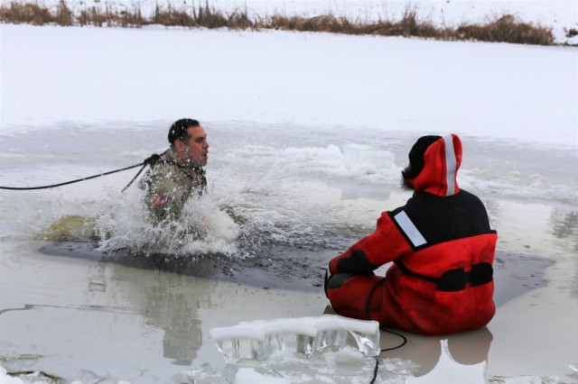 A Soldier takes the plunge into a hole cut into an ice-covered Big Sandy Lake as part of cold-water immersion training for Class 19-01 of the Cold-Weather Operations Course on Dec. 13, 2018, at Fort McCoy, Wis. The Soldier was one of 38 students in the course. In addition to cold-water immersion training, students were trained on a variety of cold-weather subjects, including skiing and snowshoe training as well as how to use ahkio sleds and other gear. Training also focused on terrain and weather analysis, risk management, cold-weather clothing, developing winter fighting positions in the field, camouflage and concealment, and numerous other areas that are important to know in order to survive and operate in a cold-weather environment. The training is coordinated through the Directorate of Plans, Training, Mobilization and Security at Fort McCoy