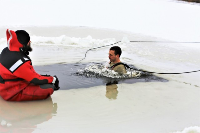 A Soldier takes the plunge into a hole cut into an ice-covered Big Sandy Lake as part of cold-water immersion training for Class 19-01 of the Cold-Weather Operations Course on Dec. 13, 2018, at Fort McCoy, Wis. The Soldier was one of 38 students in the course. In addition to cold-water immersion training, students were trained on a variety of cold-weather subjects, including skiing and snowshoe training as well as how to use ahkio sleds and other gear. Training also focused on terrain and weather analysis, risk management, cold-weather clothing, developing winter fighting positions in the field, camouflage and concealment, and numerous other areas that are important to know in order to survive and operate in a cold-weather environment. The training is coordinated through the Directorate of Plans, Training, Mobilization and Security at Fort McCoy.