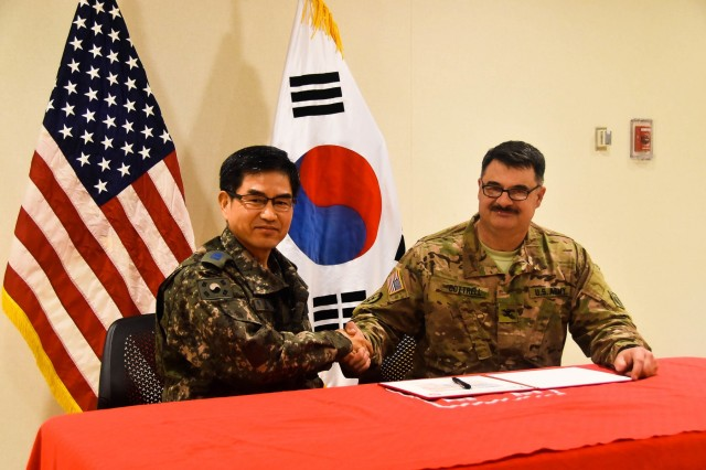 Col. Park Jong Yeon (left), Republic of Korea DCA, MND-DIA and Col. Garrett Cottrell, USACE FED deputy commanding officer- Transformation/USDCA, sign the Acceptance Release Memorandums for the SLQ031 Unaccompanied Officers Personnel Housing and UEH050 Enlisted Barracks, Camp Humphreys, South Korea, Dec 18.