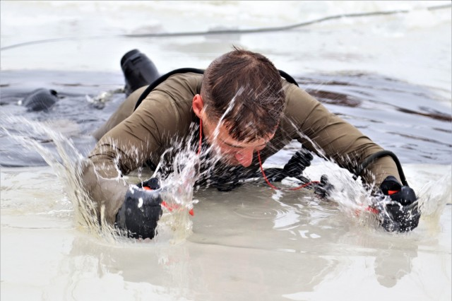 A Soldier climbs out of a hole cut into an ice-covered Big Sandy Lake after jumping in the water as part of cold-water immersion training for Class 19-01 of the Cold-Weather Operations Course on Dec. 13, 2018, at Fort McCoy, Wis. The Soldier was one of 38 students in the course. In addition to cold-water immersion training, students were trained on a variety of cold-weather subjects, including skiing and snowshoe training as well as how to use ahkio sleds and other gear. Training also focused on terrain and weather analysis, risk management, cold-weather clothing, developing winter fighting positions in the field, camouflage and concealment, and numerous other areas that are important to know in order to survive and operate in a cold-weather environment. The training is coordinated through the Directorate of Plans, Training, Mobilization and Security at Fort McCoy. (U.S. Army Photo by Scott T. Sturkol, Public Affairs Office, Fort McCoy, Wis.)