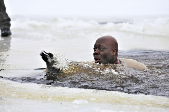 A Soldier prepares to climb out of a hole cut into an ice-covered Big Sandy Lake after jumping in the water as part of cold-water immersion training for Class 19-01 of the Cold-Weather Operations Course on Dec. 13, 2018, at Fort McCoy, Wis. The Soldier was one of 38 students in the course. In addition to cold-water immersion training, students were trained on a variety of cold-weather subjects, including skiing and snowshoe training as well as how to use ahkio sleds and other gear. Training also focused on terrain and weather analysis, risk management, cold-weather clothing, developing winter fighting positions in the field, camouflage and concealment, and numerous other areas that are important to know in order to survive and operate in a cold-weather environment. The training is coordinated through the Directorate of Plans, Training, Mobilization and Security at Fort McCoy. (U.S. Army Photo by Scott T. Sturkol, Public Affairs Office, Fort McCoy, Wis.)