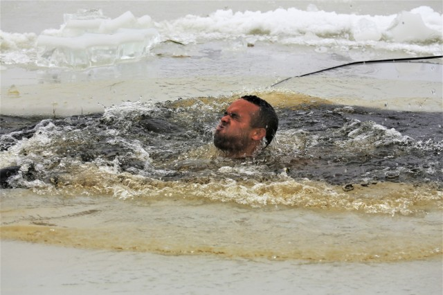 A Soldier takes the plunge into a hole cut into an ice-covered Big Sandy Lake as part of cold-water immersion training for Class 19-01 of the Cold-Weather Operations Course on Dec. 13, 2018, at Fort McCoy, Wis. The Soldier was one of 38 students in the course. In addition to cold-water immersion training, students were trained on a variety of cold-weather subjects, including skiing and snowshoe training as well as how to use ahkio sleds and other gear. Training also focused on terrain and weather analysis, risk management, cold-weather clothing, developing winter fighting positions in the field, camouflage and concealment, and numerous other areas that are important to know in order to survive and operate in a cold-weather environment. The training is coordinated through the Directorate of Plans, Training, Mobilization and Security at Fort McCoy. (U.S. Army Photo by Scott T. Sturkol, Public Affairs Office, Fort McCoy, Wis.)