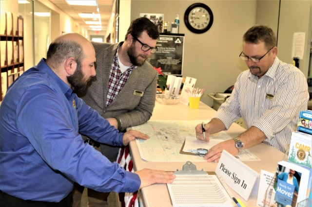 (From left) Program Manager Jaime Herrera, Garrison Sexual Harassment Assault Response Program Victim Advocate Ryan Harvey, and Fort McCoy Army Community Service (ACS) Director Kevin Herman review the day's activities planned Dec. 18, 2018, at Fort McCoy, Wis. Herrera is new to the Fort McCoy ACS office, and he formerly served at Fort McCoy with the 181st Multi-Functional Training Brigade. Herrera will support mobilization/deployment readiness, Army Family Action Plan, and Army Family team-building activities at ACS. (U.S. Army Photo by Scott T. Sturkol, Public Affairs Office, Fort McCoy, Wis.)