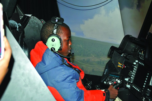 Yai Tong, 11, flies the AH -64 Apache simulator during the Cub Scout Pack 78 visit Dec. 28.