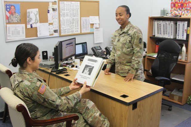 Cpt. India T. Simpson (right), commander, Headquarters and Headquarters Battery, 10th Army Air and Missile Defense Command, and Sgt. Evelin Bullard, a human resources specialist with 10th AAMDC, discuss holiday block leave for Soldiers, Dec. 6, at Rhine Ordnance Barracks, Germany.