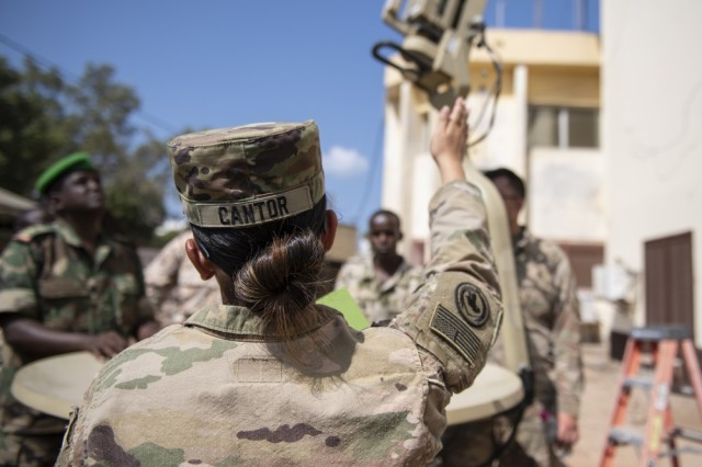 U.S. Army Spc. Christine Cantor, assigned to the Combined Joint Task Force-Horn of Africa communications directorate, explains safety while setting up a satellite unit during an Africa Data Sharing Network (ADSN), version two, information exchange with Djibouti Army (FAD) soldiers at FAD Headquarters, Djibouti, Dec. 26, 2018. The ADSN works as an internal network that the African Union Mission in Somalia troop-contributing countries can use to communicate and share information amongst each other.