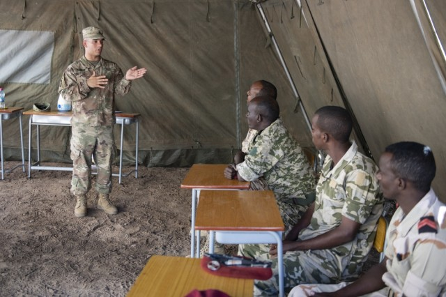 U.S. Army Staff Sgt. Jerry Alvarez, Combined Joint Task Force-Horn of Africa communications directorate NCO in charge, gives opening remarks during an Africa Data Sharing Network (ADSN), version two, information exchange with Djibouti Army (FAD) soldiers at FAD Headquarters, Djibouti, Dec. 26, 2018. The ADSN works as an internal network that the African Union Mission in Somalia troop-contributing countries can use to communicate and share information amongst each other.