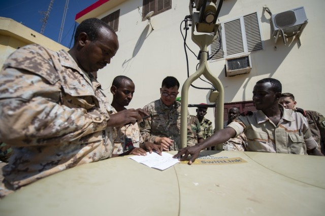 U.S. Army Spc. Legend Khotsombath, assigned to the Combined Joint Task Force-Horn of Africa communications directorate, explains parts of a satellite unit during an Africa Data Sharing Network (ADSN), version two, information exchange with Djibouti Army (FAD) soldiers at FAD Headquarters, Djibouti, Dec. 26, 2018. The ADSN works as an internal network that the African Union Mission in Somalia troop-contributing countries can use to communicate and share information amongst each other.