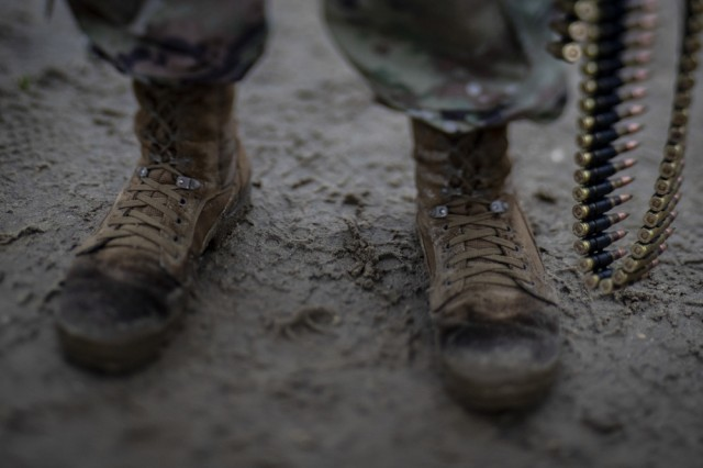 The U.S. Army Research, Development and Engineering Command Soldier Center at Natick is testing new Army Combat Boot (ACB) prototypes at three different basic training and active duty installations over the next four months. The effort will gather Soldier feedback toward development of improved footwear. Pictured, a U.S. Army Soldier from the 1-114th Infantry Regiment stands in the mud holding 7.62mm ammunition during M240 machine gun weapons training on Joint Base McGuire-Dix-Lakehurst, N.J., Nov. 6, 2018.