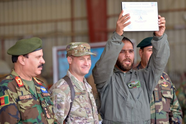 A graduate from UH-60 Mission Qualification Training proudly holds his certificate of training at a graduation ceremony May 8 at Kandahar air base, Afghanistan. Thirty-one Afghan air crew members graduated during the ceremony.