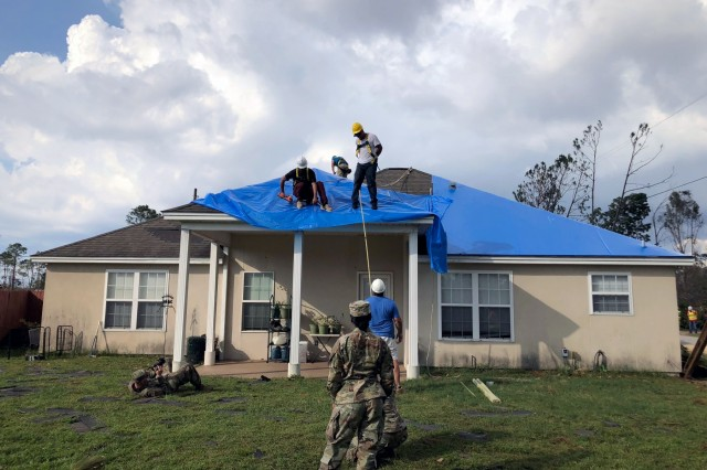 U.S. Army Corps of Engineers contractors in Panama City, Fla., install reinforced plastic sheeting Oct. 19, 2018, for the first home to benefit from Operation Blue Roof, a program for homeowners or landlords affected by Hurricane Michael. The program, offered by FEMA, provides a temporary covering of reinforced blue plastic sheeting to help reduce further damage to property until permanent repairs can be made. (Photo by Luciano Vera)