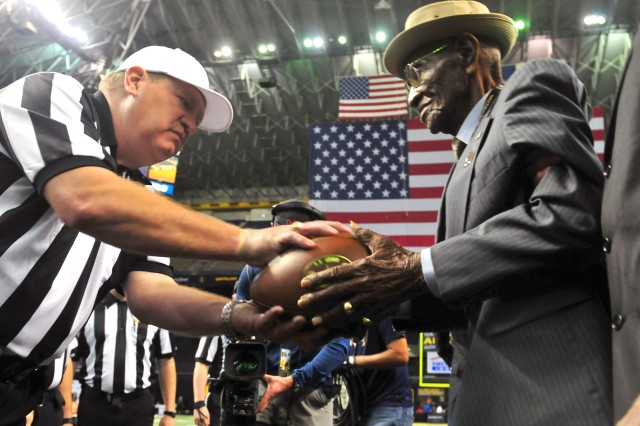 Richard Overton, right, a World War II veteran who lived to be the oldest American man, presents the game ball before the U.S. Army All-American Bowl in San Antonio, Texas, Jan. 9, 2016. Overton died Dec. 27, 2018, at the age of 112. He will be buried at the Texas State Cemetery in Austin on Jan. 12, 2019.