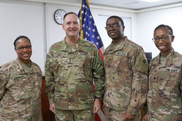 Sgt. 1st Class Vanessa Chambers, Staff Sgt. Titus Johnson, and Spc. Charmaine Amos, 184th Sustainment Command paralegal specialists, pause for a photo with The Judge Advocate General of the U.S. Army, Lt. Gen. Charles N. Pede, at Camp Arifjan, Kuwait Jan. 8, 2019. (U.S. Army National Guard photo by Staff Sgt. Veronica McNabb)