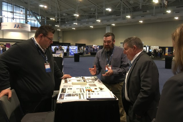 Michael Nikodinovski RDECOM Ground Vehicle Systems Center (left) and Dr. James Zunino RDECOM Armaments Center (center) discuss Army additive manufacturing examples with Dr. Thomas Russell (DASA(R&T)) at the Defense Manufacturing Conference Army ManTech Program booth.