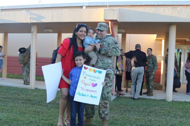 Patricia Diaz (left), and Sgt. Delwin Gonzalez (right) together hold their one year old son Alexis (center), while their six year old son holds two welcome home banners, during the return of the 613th Military Police Company to Puerto Rico, Jan 15, after successfully completing their mission at the Guantanamo Naval Base.