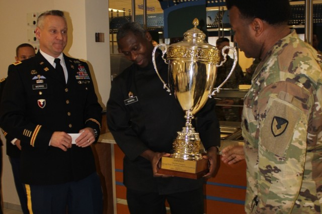 Col. Grant L. Morris, commander 405th Army Field Support Brigade (left), presents the U.S. Army Europe-level Philip A. Connelly Award trophy to Sgt. 1st Class Timothy Morris, dining facility manager (middle), while Chief Warrant Officer 4 Jeffery Stubbs, food services advisor, 405th AFSB, looks on, at Kleber Kaserne, Kaiserslautern, Jan. 11. The Philip A. Connelly award was established in 1968, to encourage outstanding professionalism in Army food service teams and recognize excellent performance.  The dining facility will compete for the 2019 Department of the Army level Connelly Award as one of the six finalists in March.