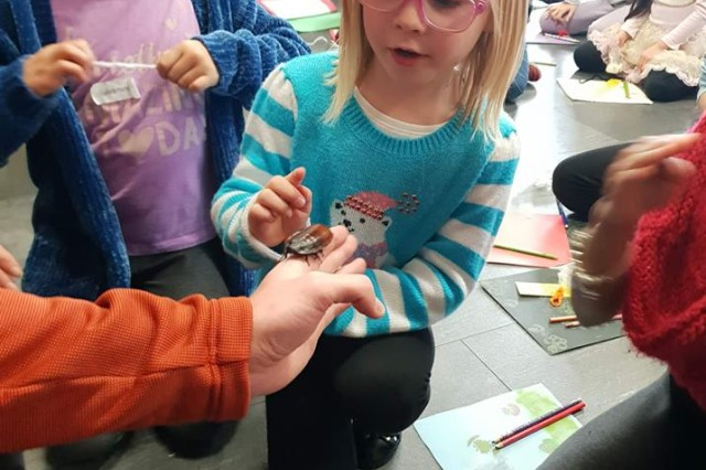 A Daisy from the Landstuhl Girl Scouts troop is inspecting the cockroach.