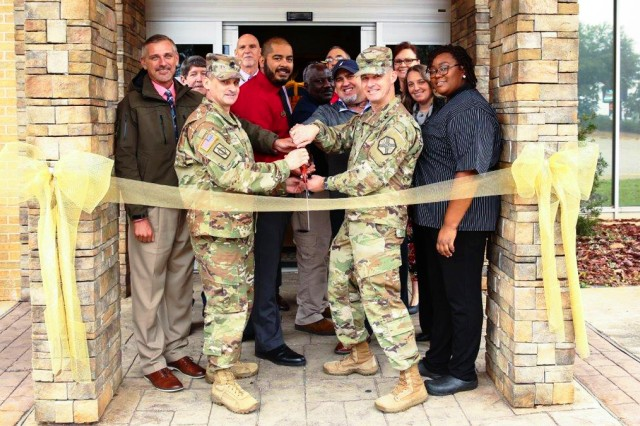 Col. Brian E. Walsh, Fort Rucker garrison commander, and Sgt. Maj. Steven Rogers, Directorate of Public Safety sergeant major, cut the ribbon during The Landing Zone's grand re-opening ceremony Jan. 14.