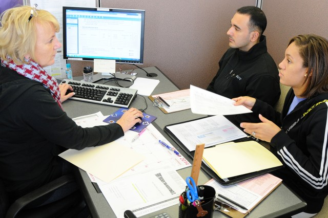 Gail Evelyn, then a tax preparer at the Fort Rucker Tax Center, helps then-CW2 Ralph Hernandez and his wife, Brittany, with their tax return in this file photo.
