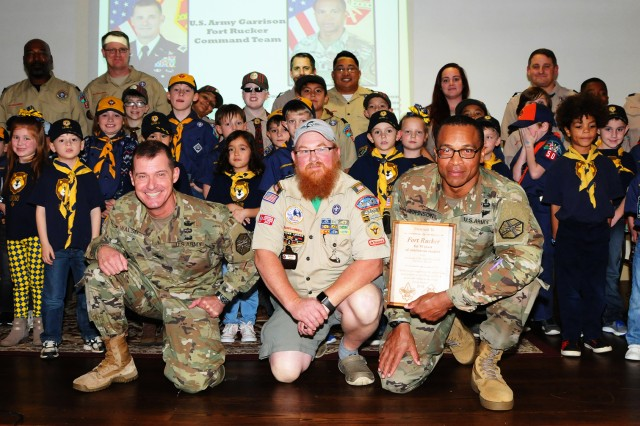 Col. Brian E. Walsh, garrison commander, Chris Wood, Boy Scout Troop 50 troop master, and Command Sgt. Maj. Jasper C. Johnson, garrison command sergeant major, pose for a photo with assembled Scouts during the Dec. 20 ceremony at Wings Chapel where Scouts thanked the garrison for 50 years of continuous support.