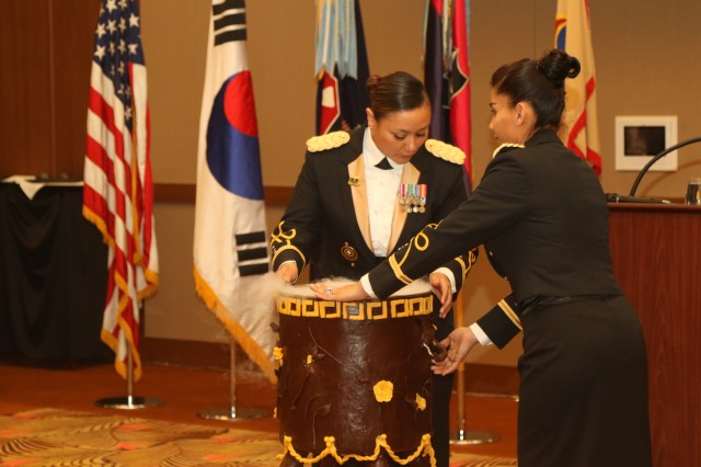 """Chief Warrant Officer 2 Rosa Villagran, Command Food Advisor for 1st Theater Tactical Signal Brigade and co-coordinator of the Food Service Ball (left) and Chief Warrant Officer 2 Karena Apodaca, Command Food Advisor for 403rd Army Sustainment Command and co-coordinator of the Food Service Ball, bring out the container for the """"grog"""" during the Food Service Ball on Camp Humphreys, Jan. 11, 2019. The """"grog"""" is a traditional drink often served during military service balls. 1st Theater Tactical Signal Brigade hosted a Food Service Ball in recognition of the hard work from Culinary Specialists throughout South Korea over the last year."""