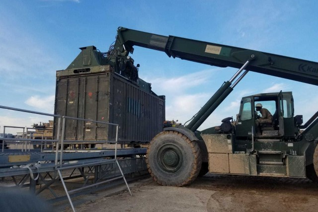 Spc. Abdel Sawadogo, 151st Movement Control Team, moves containers with the RT240, rough terrain container handler,  in Southwest Asia Jan. 14, 2019.  (U.S. Army photo Sgt. Jose Lindbetancourt)