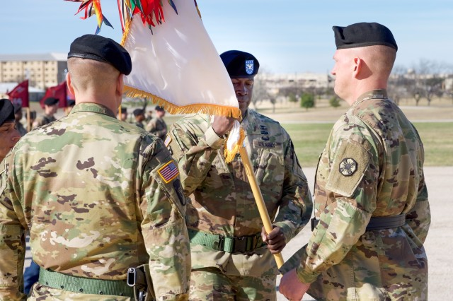 Outgoing 1st Medical Brigade Commander, Col. Anthony Nesbitt, passes the 1st Med Bde colors to Brig. Gen. Darren Werner, commanding general of the 13th Expeditionary Sustainment Command, during Thursday's Change of Command ceremony on Sadowski Field on Fort Hood, Texas January 17, 2019.