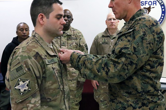 Marine Brig. Gen. Daniel Conley, commander, Bagram Airfield, Afghanistan, presents Shane Markel, contract analyst, Area Support Group-Afghanistan, with the Achievement Medal for Civilian Service, Dec. 15, 2018, in the U.S. Forces Command-Afghanistan, BAF, headquarters building. Markel, who normally works at Defense Contract Management Agency in Detroit, Michigan, was recognized for his work from Sept. 15-Nov. 28 which led to the validation of a multi-billion dollar Logistics Civil Augmentation Program contract that provides base life services to about 45,000 personnel at 12 locations across Afghanistan in support of the Resolute Support Mission. The RSM is a NATO-led, non-combat mission to train, advise and assist the Afghan National Defense and Security Forces to ensure that Afghanistan is never again a safe haven for terrorism.