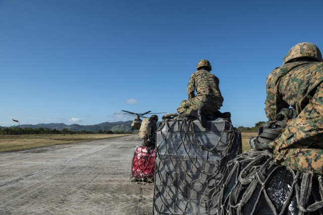 Agents from Panama's National Border Service wait to load slings onto a U.S. Army CH-47 Chinook headed to the Darien Province in the Republic of Panama, Jan. 11, 2019. The agents loaded construction supplies such as cinderblocks, concrete and rebar onto the aircraft which then carried the supplies into the jungle.