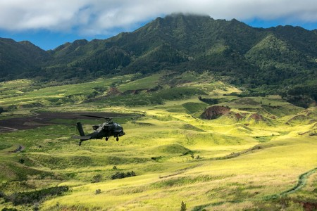 A U.S. Army AH-64D Apache helicopter flies in formation for the 25th Infantry Division Review over Schofield Barracks, Hawaii, Dec. 21, 2018. The division's activation date is Oct. 1, 1941.