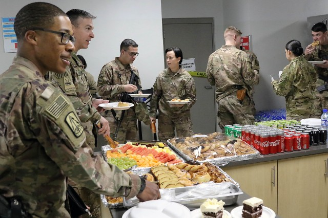 Attendees partake in cake and refreshments following the Dr. Martin Luther King Jr. observance ceremony Jan. 21 at the Morale, Welfare, and Recreation center, Bagram Airfield, Afghanistan. (Photo by Jon Micheal Connor, Army Public Affairs)