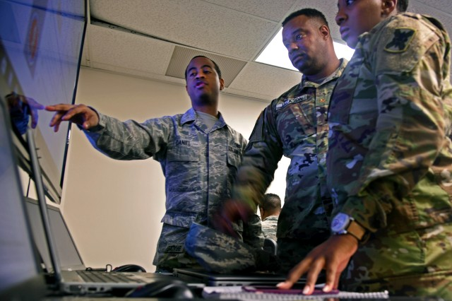 Senior Airman David Daniel, left, with the Maryland Air National Guard's 275th Cyber Operations Squadron, points out key pieces of information on cyber defense operations to Army Maj. Steven Jackson, assistant intelligence officer with with the Mississippi National Guard, and Army Staff Sgt. Nyesha Bradley, with the Louisiana Army National Guard's D Company, 769th Brigade Engineer Battalion, during exercise Cyber Shield 17 at Camp W.G. Williams in Bluffdale, Utah, in April 2017. As the cyber threat has evolved, so too have the National Guard's cyber units and capabilities, said Guard officials during a recent cyber roundtable discussion at the Pentagon.