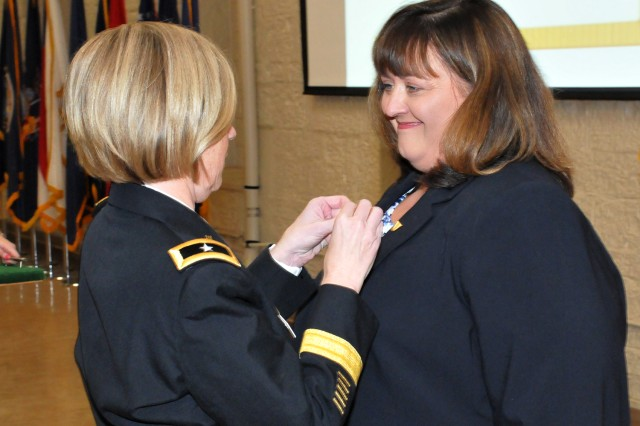 Brig. Gen. Michelle M. T. Letcher, Commander, Joint Munitions Command, pins the Senior Executive Service pin on JoEtta Fisher, during the official promotion ceremony at the Rock Island Arsenal, Jan. 22.