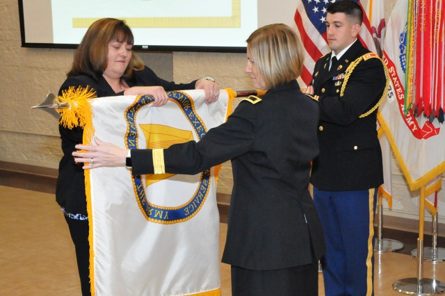 JoEtta Fisher, with assistance from Brig. Gen. Michelle M.T. Letcher, Commander, Joint Munitions Command, unfurls her Senior Executive Service flag during the official promotion ceremony at the Rock Island Arsenal, Jan. 22.