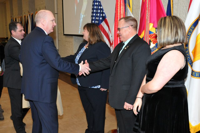 JoEtta Fisher, Joint Munitions Command, her husband, Jeff, and daughter, Macy Taschler, greet distinguished guests following her official SES promotion ceremony at the Rock Island Arsenal, Jan. 22.