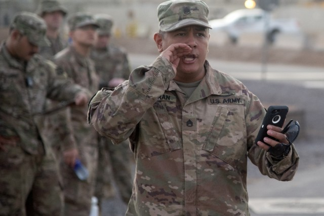 """U.S. Army Staff Sgt. Zachary Fejeran, Bowie Company, 1st Battalion, Task Force Alamo, Texas National Guard, assigned to Combined Joint Task Force-Horn of Africa (CJTF-HOA), Djibouti, calls out times during a """"ruckrun"""" for the German Armed Forces Badge (GAFB) for Military Proficiency in Djibouti, Jan. 15, 2019. The GAFB is awarded to and worn by German service members of all ranks. Allied service members may also be awarded the badge, subject to their nations' uniform regulations."""