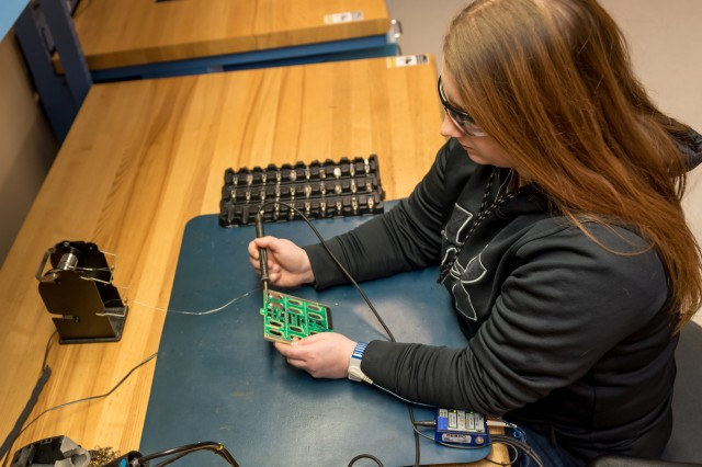 Amanda Cortino, electronics mechanic, replaces battery cells on a circuit card from an airborne radio system. Cortino and three coworkers came up with a new way of fixing faulty cards to cut costs and save time.