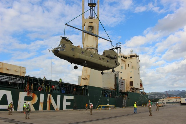 A ship's crane lowers a Chinook helicopter during port operations in support of the Hawaii Army National Guard at Pearl Harbor on Jan. 6.