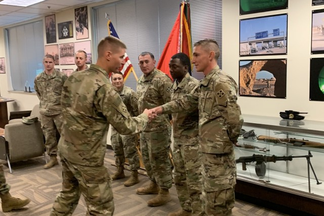 Col. Dave Zinn, left, commander of the 2nd Infantry Brigade Combat Team, 4th Infantry Division, presents a coin to Pfc. Adrian Vetner, right, a horizontal construction engineer with Alpha Company, 52nd Brigade Engineer Battalion, 2nd IBCT, Jan. 9, 2019, at the brigade headquarters building on Fort Carson, for his recent actions in helping others.