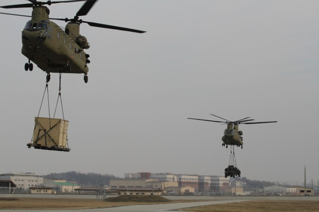 CH-47 Chinook helicopters take off after Soldiers from the 123rd Brigade Support Battalion, 3rd Brigade Combat Team, 1st Armored Division, successfully attach equipment during sling load operations training Jan. 7 at Camp Humphreys, Republic of Korea. Sling load operations test Soldiers' ability to move equipment from location to location. (U.S. Army photo by Pfc. Edwin Petzke, 20th Public Affairs Detachment)