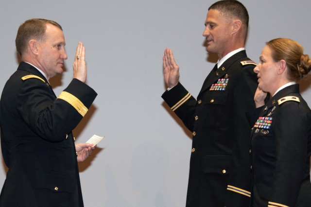 Jared and Josephine Thompson recite the officer's oath of office, administered by Brig. Gen. Thomas Todd, program executive officer for aviation, during a dual promotion ceremony Jan. 4 in Bob Jones Auditorium. Jared became a chief warrant officer 5; and Josephine, who goes by Jo, became a colonel.