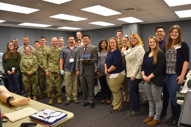 Jay Wang, product manager for the U.S. Army Medical Materiel Development Activity, poses with the Medical Hands-free Unified Broadcast device in Fort Rucker, Ala., with Rachel Kinsler, U.S. Army Aeromedical Research Laboratory study team lead and Army Col. Jonathan Taylor, commander of USAARL, along with the rest of the team who made the MEDHUB Hospital study possible.