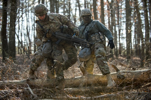 "Spc. Bethany Brennan, Sgt. Cheikh Fall and a fellow U.S. Army Reserve Soldier from the 200th Military Police Command's Headquarters Company, cross over a log on a land navigation course during a field training exercise at Fort Meade, Md., Jan. 10, 2019. Army Reserve units are involved in an escalating number of training exercises as part of a ""cultural change"" to emphasize readiness, said Lt. Gen. Charles Luckey, chief  of the Army Reserve."