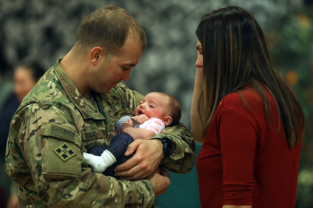 Capt. Harold Rivard, 2-12th Infantry, greets his baby daughter and wife upon returning to Fort Carson, Colo., Nov. 17, 2018, after a nine-month deployment in support of Resolute Support with the 2nd IBCT, 4th Inf. Div. Under the Army's new parental leave policy, Soldiers like Rivard can now apply for 21 days of parental leave as a secondary caregiver or 42 days if designated primary caregiver.