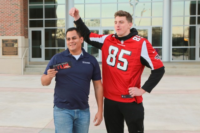 "FORT BENNING, Ga. (Jan. 29, 2019) -- Erasmo ""Moe"" Espino, 2014 Tillman Foundation scholar and 15-year Army veteran, receives two tickets to the 2019 Super Bowl from Eric Saubert, Atlanta Falcons tight end, at McGinnis-Wickam Hall, Fort Benning, Georgia, during the NFL Salute to Service Jan. 29, 2019. The NFL and USO came together to throw the event, which included a meet and greet with Atlanta Falcons players and cheerleaders. (U.S. Army photo by Markeith Horace, Maneuver Center of Excellence, Fort Benning Public Affairs)"