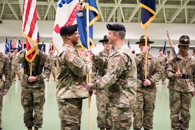 Brig. Gen. Andy Munera, USACBRNS commandant, right, passes the regimental colors to Regimental Command Sgt. Maj. Christopher Williams Tuesday in Nutter Field House to signify his assumption of responsibility as regimental command sergeant major.