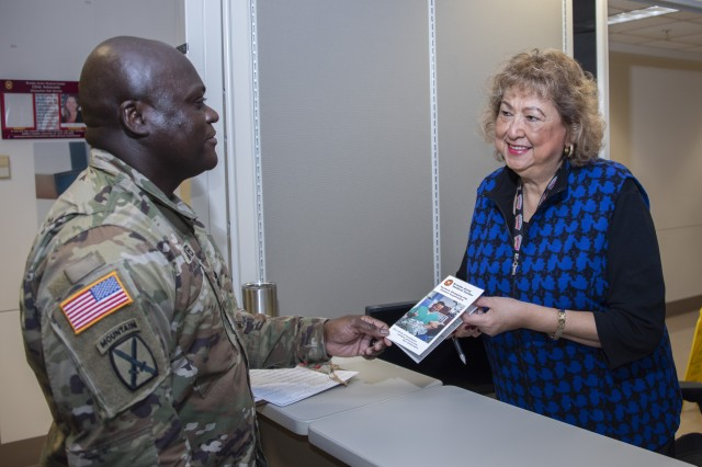 Cynthia Barrera, volunteer, hands Sgt. 1st Class Andrew Gittens, Medical Education Training Campus instructor and writer, a Mystery Shopping Patient Experience pamphlet at Brooke Army Medical Center, Fort Sam Houston, Texas, Jan. 25, 2019. The program enlists patients to anonymously evaluate the care they receive at medical appointments.