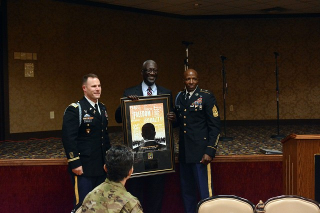 Former Fort Jackson commanding general, retired Maj. Gen. Abraham Turner (center) is presented with a token of appreciation for speaking during the Martin Luther King Jr. birthday observance luncheon at the NCO Club Jan. 25 by Col. Patrick Aspland, left, and Command Sgt. Maj. Roosevelt Whetstone.