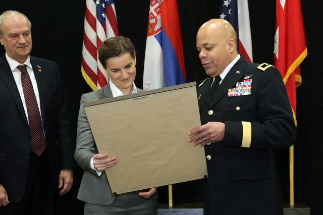 Maj. Gen. John C. Harris Jr., Ohio adjutant general, presents a gift to Serbian Prime Minister Ana Brnabic as Serbian Ambassador to the U.S. Djerdj Matkovic looks on, Jan. 28, 2019, at the Ohio National Guard Joint Force Headquarters located at the Maj. Gen. Robert S. Beightler Armory in Columbus, Ohio. Ohio and Serbia have partnered since 2006 under the State Partnership Program (SPP), managed by the National Guard Bureau. The goal of the SPP is to link a state's National Guard with a partner country to promote regional stability and develop civil and military relationships.
